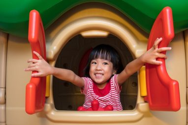 Asian Chinese little girl playing in toy house at indoor playground.